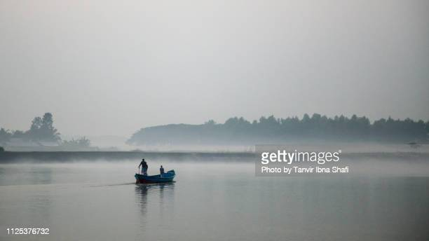 small motorboat moving through the padma river in a foggy winter morning - winter bangladesh stock photos and pictures