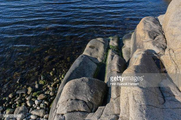 small mountain and rocks at the seashore - finn bjurvoll stock pictures, royalty-free photos & images