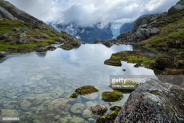 Small mountain lake in Jostedalsbreen National Park with Briksdalsbreen glacier in background, Sogn og Fjordane, Norway