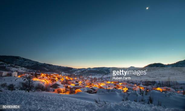 Small mountain village at dusk during winter with city lights turned on