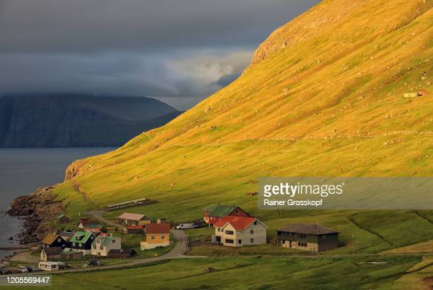 a small northern village on the foot of a mountain that is illuminated by the warm light of the setting sun - rainer grosskopf stock-fotos und bilder