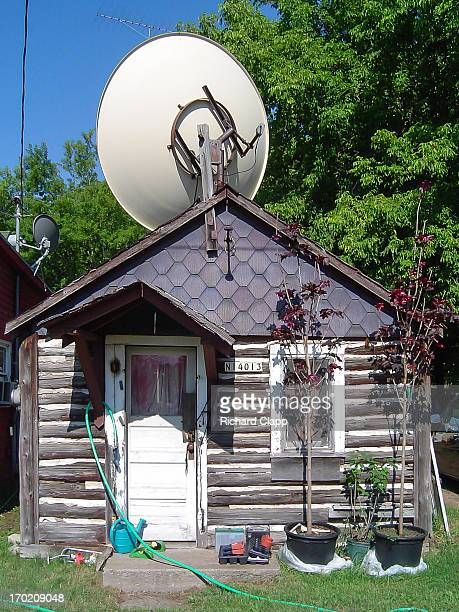 Small, old log cabin with large satellite dish. Located in the Northwoods of Wisconsin. Two trees in plastic buckets, along with watering can,...