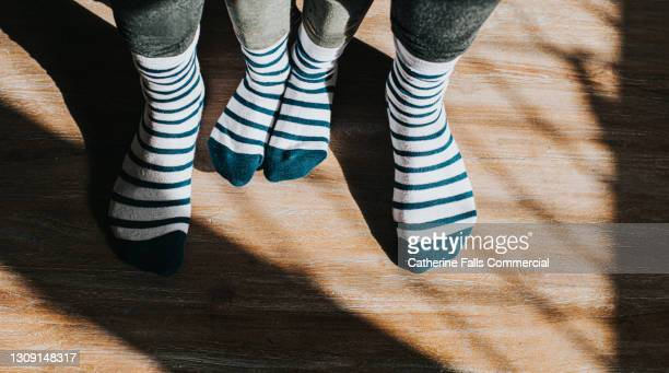 a small pair of feet between bigger feet in identical matching stripy socks - human joint stock pictures, royalty-free photos & images