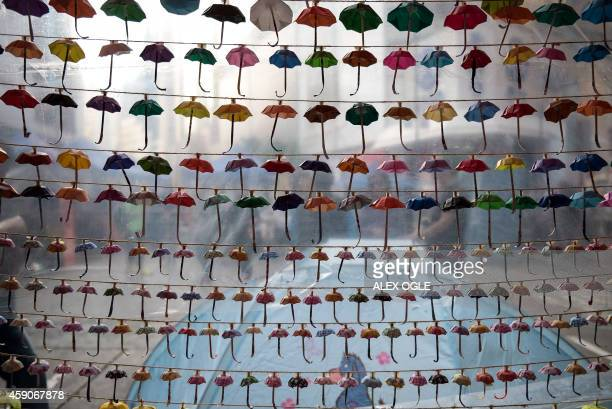 Small paper umbrellas -- symbols of the pro-democracy protests in Hong Kong -- are strung up in a display at the site of protest in the Causeway Bay...