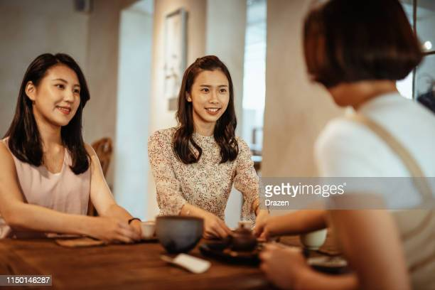 Small party in tea house with three Asian women.