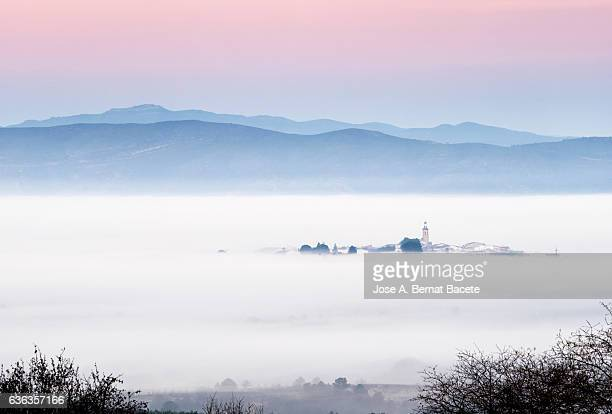 Small people in a valley surrounded with fog and with mountains to the dawn