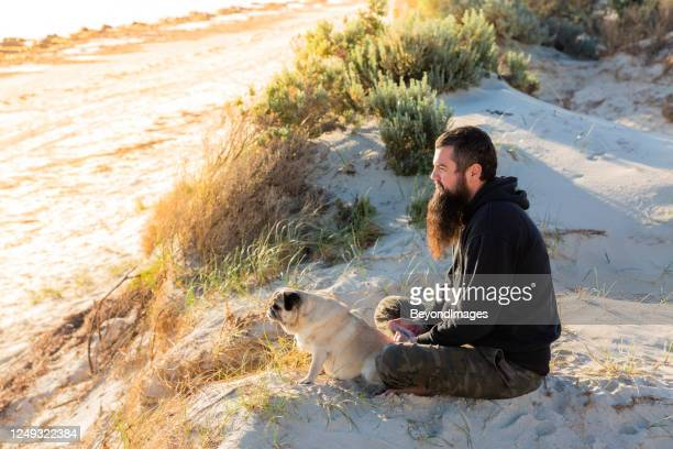 small pet female pug with bearded adult man sitting cross-legged on sand dune - australia stock pictures, royalty-free photos & images