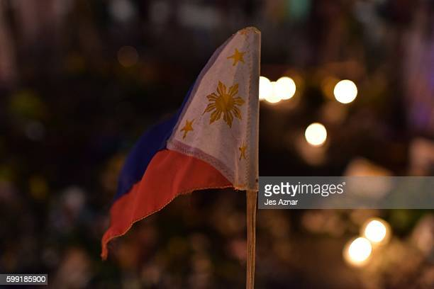 Small Philipphine flag is hoisted in front of flowers and candles at the blast site that killed 14 people in Davao city on September 4, 2016. The...
