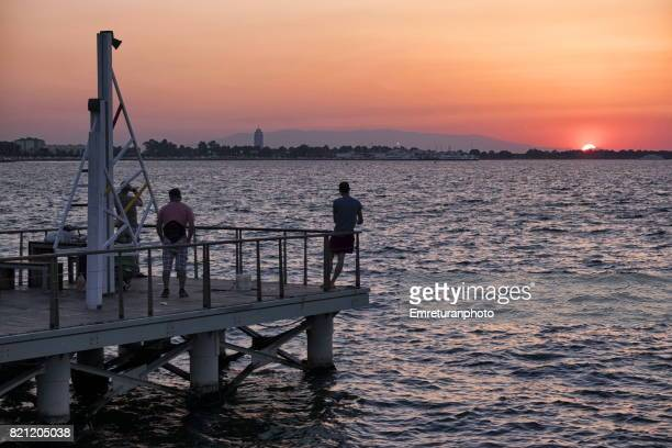 small pier for fisherman at sunset in izmir. - emreturanphoto stock pictures, royalty-free photos & images