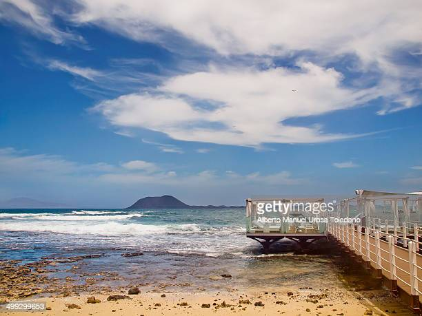 CONTENT] A small pier with deck chairs and a bar on it where holiday makers can enjoy a relaxing sunbath while they watch the Atlantic Ocean and the...