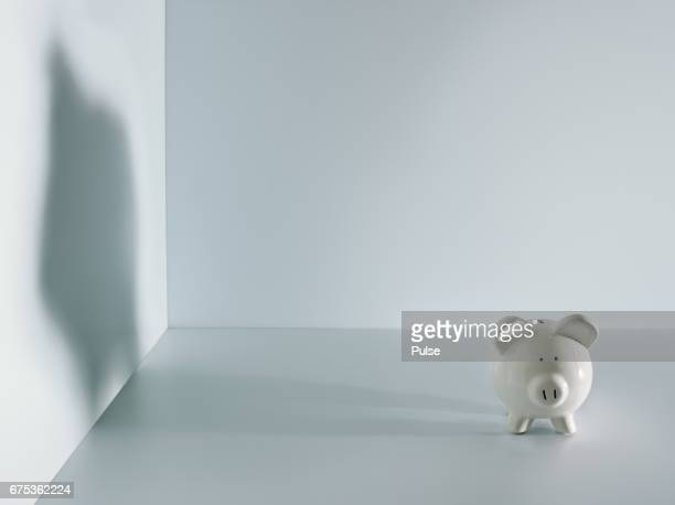 Small piggy bank with large shadow of it.