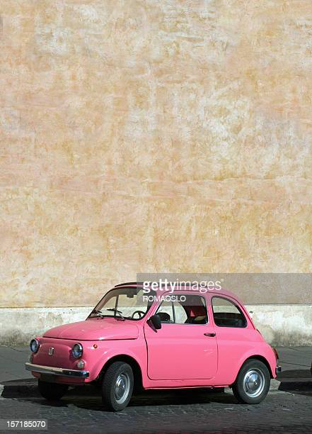 Small pink vintage Fiat car in Rome, Italy