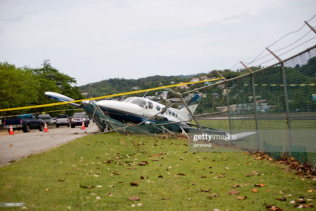 small plane crashes through fence on highway in emergency landing : Stock Photo
