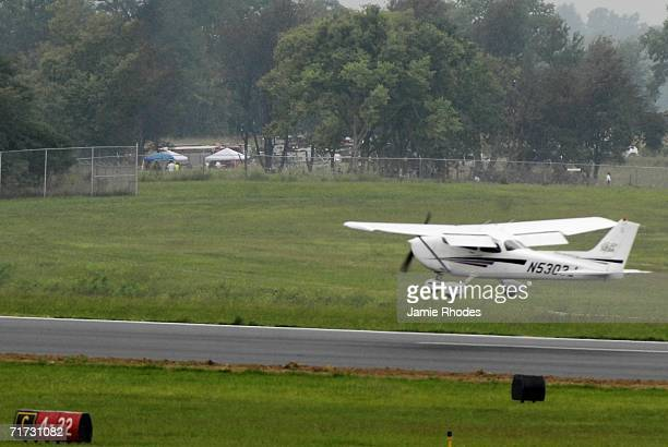 A small plane lands on runway 22 at Lexington Blue Grass Airport as National Transportation Safety Board investigators work in a makeshift camp...