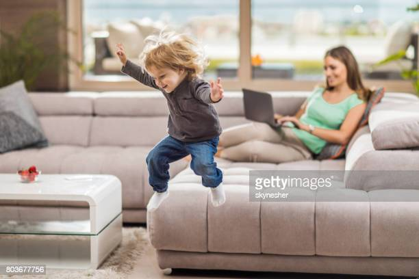 small playful boy having fun while jumping of the sofa in the living room. - women of penthouse stock photos and pictures
