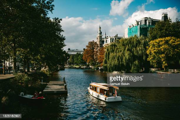a small pleasure boat sails on a canal in the old town of amsterdam in the netherlands in autumn, when the leaves of the trees change color - amsterdam stock pictures, royalty-free photos & images