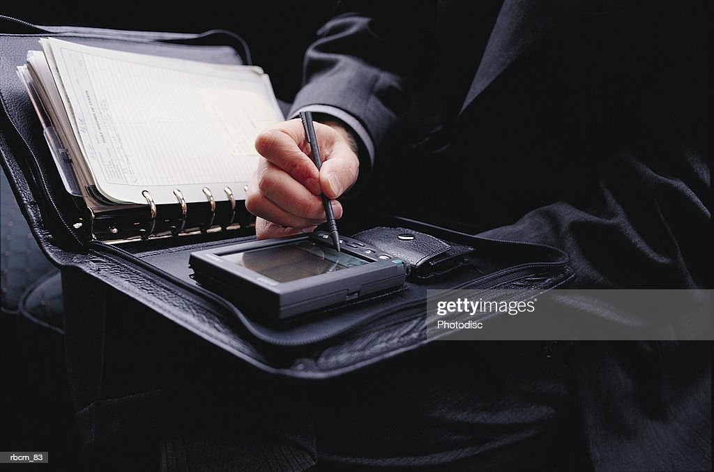 A small, portable computer is being used by a businessman dressed in a black suit to do work. : Stockfoto