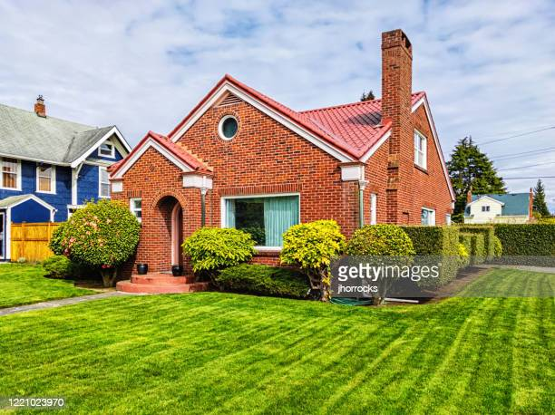 small red brick house with green grass - brick house stock pictures, royalty-free photos & images