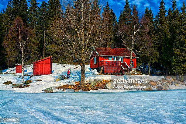 Small red cabin belonging to DNT, the tourist association, is seen at the end of the frozen lake Sandungen in the Oslo forests. A skier is walking...