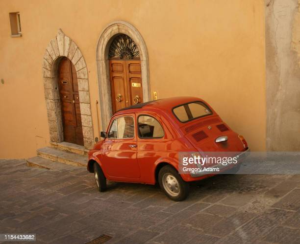 small red car parked in front of a medieval building in small red car parked in front of a medieval building in san gimignano, italy - サンジミニャーノ ストックフォトと画像