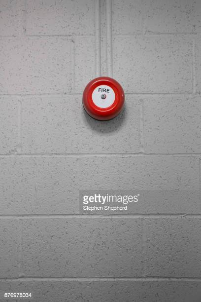 A small red fire alarm bell on a wall.