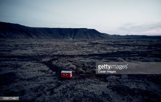 small red house in dark dry terrain surrounded by hills - lava plain stock pictures, royalty-free photos & images