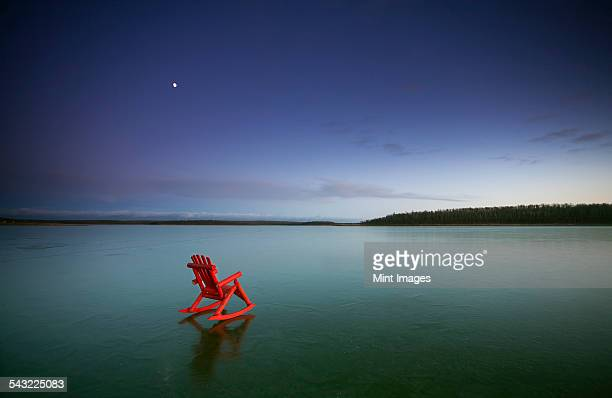 A small red rocking horse, on a frozen lake.