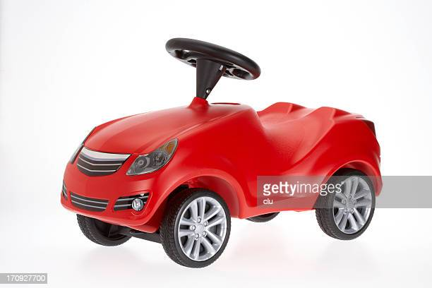 Small red toy car side view on white background
