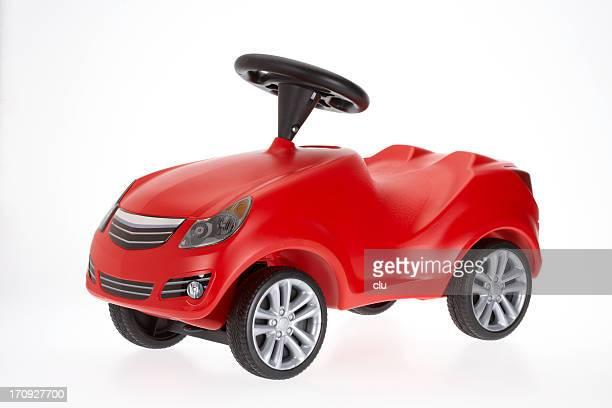 Coche de juguete pequeño rojo vista lateral sobre fondo blanco