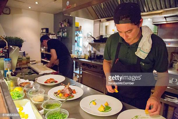 Small restaurant chef plating dishes during evening service