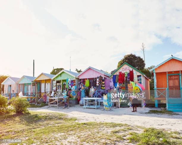 a small row of colourful caribbean beach huts start to open ready for the holiday makers and customers - antigua & barbuda stock pictures, royalty-free photos & images