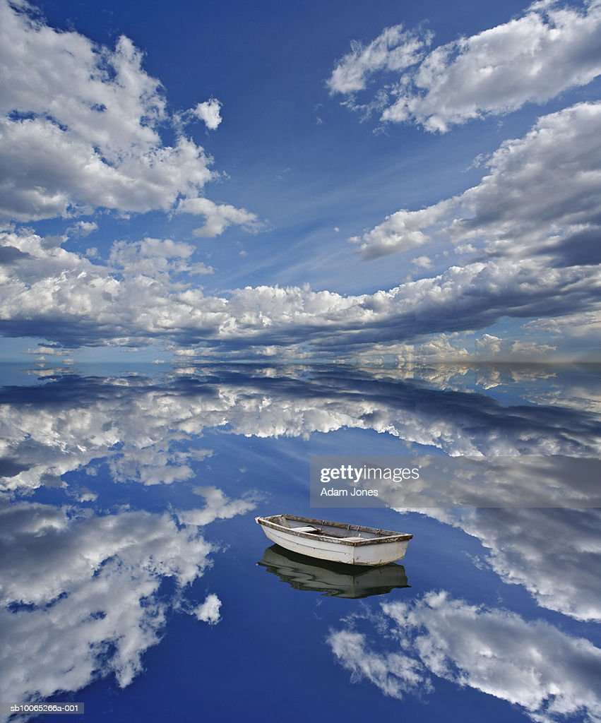 Small rowing boat with reflection of clouds in sea : Foto stock