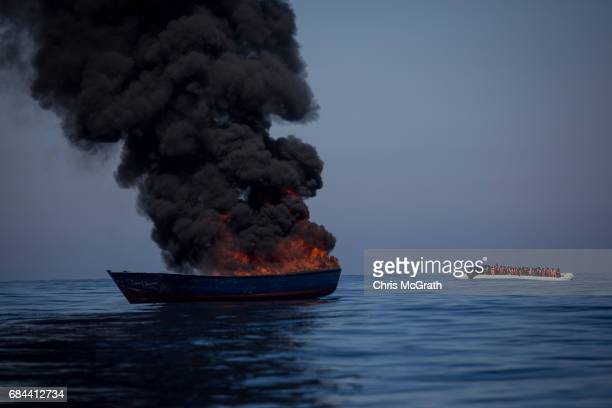 A small rubber boat overcrowded with refugees and migrants passes a boat set alight by rescue crews from the Migrant Offshore Aid Station Phoenix...