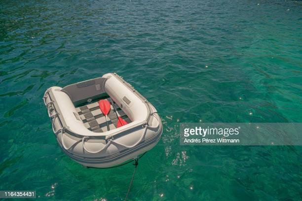 small rubber lifeboat which serves as a rescue boat or shuttle to the shore - bote inflável - fotografias e filmes do acervo