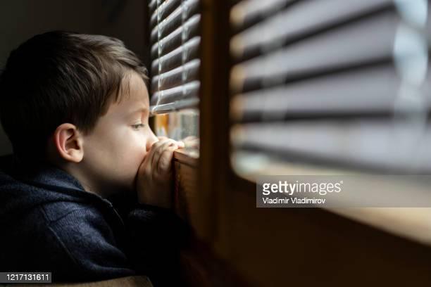 kleine droevige jongen die door het venster tijdens isolatie coronavirus kijkt. - eenzaamheid stockfoto's en -beelden