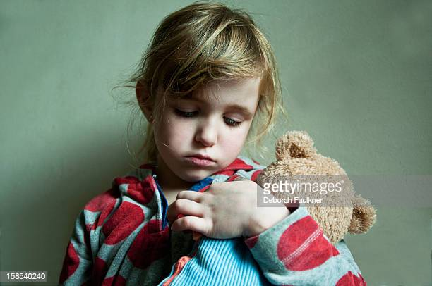 Small, sad girl cuddling a teddy