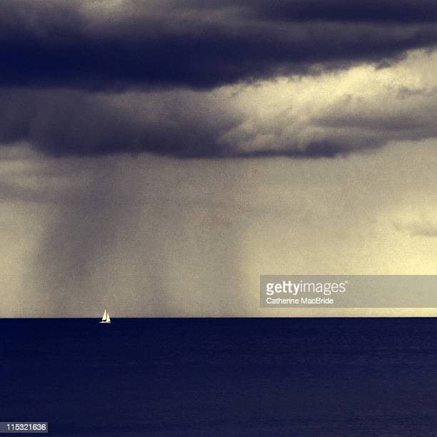 Small sail boat in stormy weather