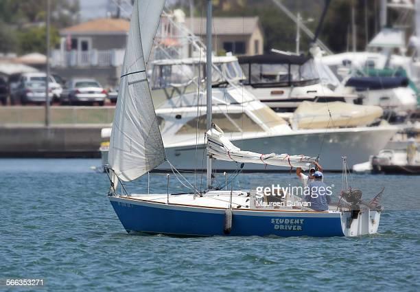 Small sailboat in a marina using only the jib having lowered the mainsail Long Beach Marina California