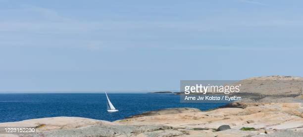 small sailboat leaning over in the wind near nordic coast landscape - arne jw kolstø stock pictures, royalty-free photos & images