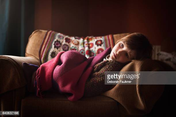 Small serious girl lounging on comfortable chair