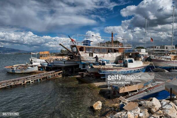 small shipyard with wooden boats on a partly cloudy day,izmir. - emreturanphoto stock pictures, royalty-free photos & images