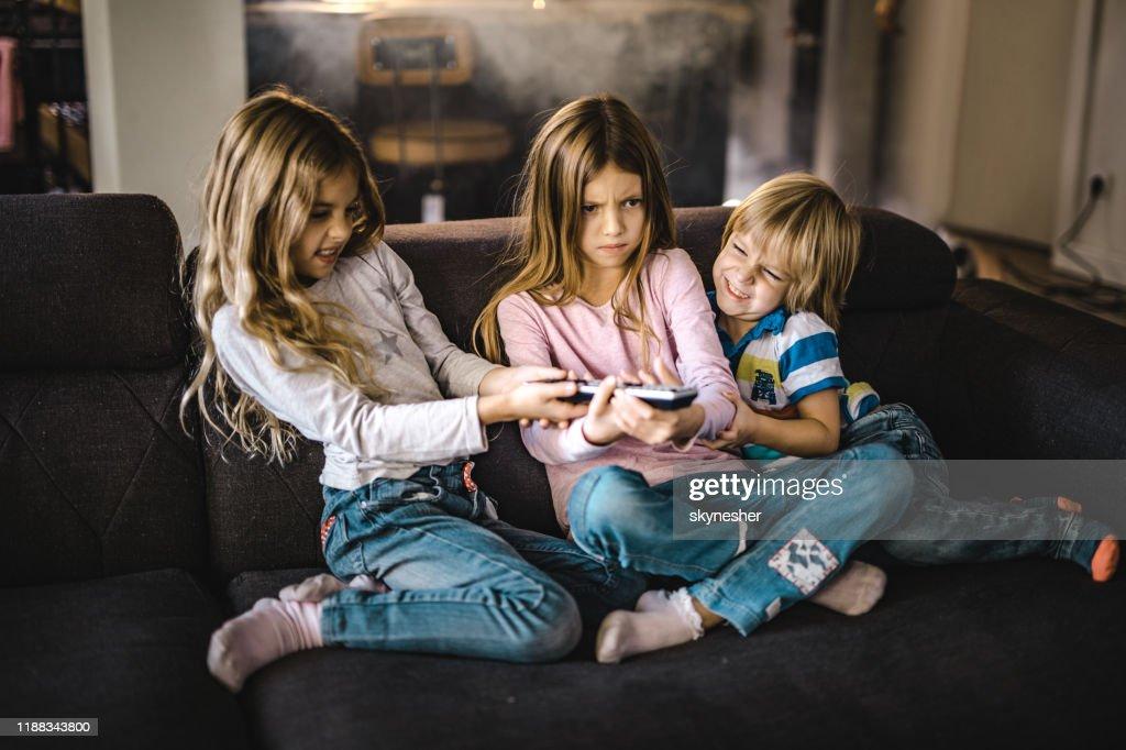 Småsyskon slåss över en fjärrkontroll i vardagsrummet. : Bildbanksbilder