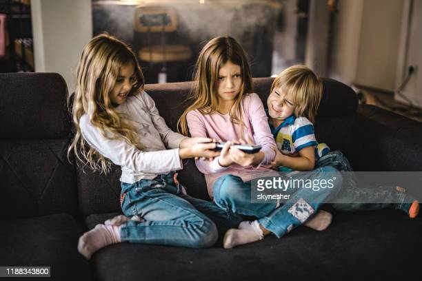 small siblings fighting over a remote control in the living room. - fighting stock pictures, royalty-free photos & images