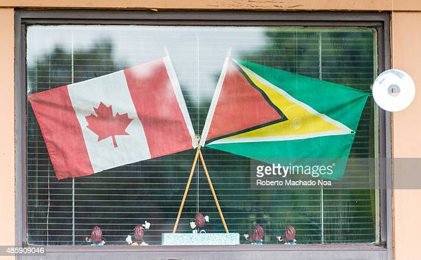 Small sized national flags of Canada and Guyana placed in crossed position on a stand seen through a glass covered frame