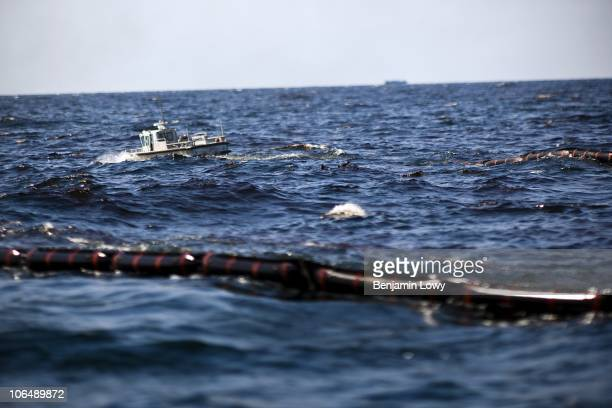 A small skiff boat attached to a larger emergency response oil skimming ship leads an oil collecting boom into the oil covered Gulf of Mexico on...