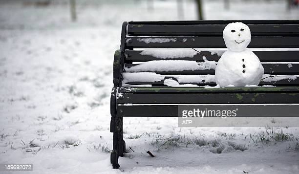 A small snow man sits on a bench in Regent's Park after snowfall in central London on January 18 2013 Snow swept across Britain forcing airports to...