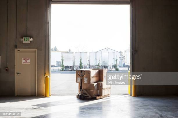 a small stack of products in boxes sitting on a manual pallet jack in a loading dock door at a distribution warehouse. - loading dock stock pictures, royalty-free photos & images