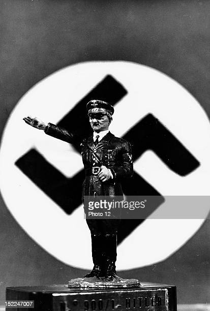 Small statue representing Adolf Hitler with the swastika in the background