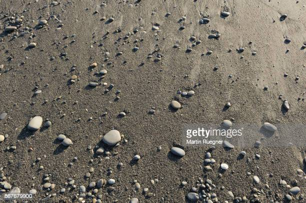 Small stones on sandy beach.