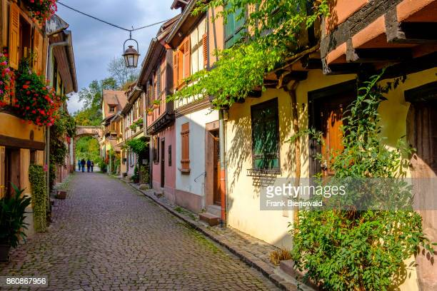 A small street is leading through the flower decorated halftimbered houses of the historical town